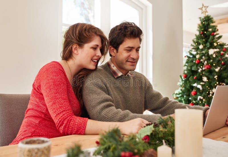 Pares jovenes en casa que hacen compras en línea para la Navidad fotos de archivo libres de regalías