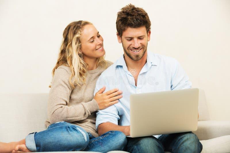 Pares jovenes en casa usando el ordenador portátil fotos de archivo libres de regalías