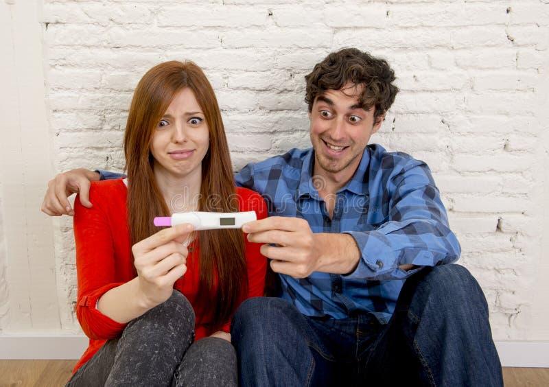 Pares jovenes en choque y sorpresa con embarazo positivo rosado de lectura asustado de la muchacha embarazada fotos de archivo