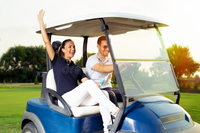Pares jovenes en cochecillo del golf fotografía de archivo