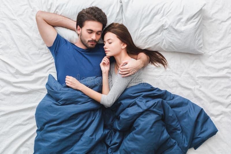 Pares jovenes en dormir del concepto de la mañana de la opinión superior de la cama fotos de archivo
