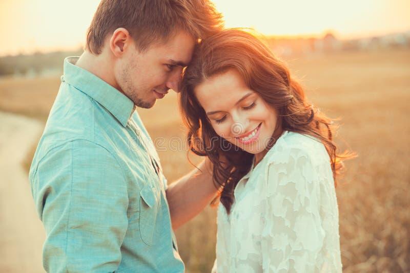 Pares jovenes en el amor al aire libre Junte el abrazo imagen de archivo