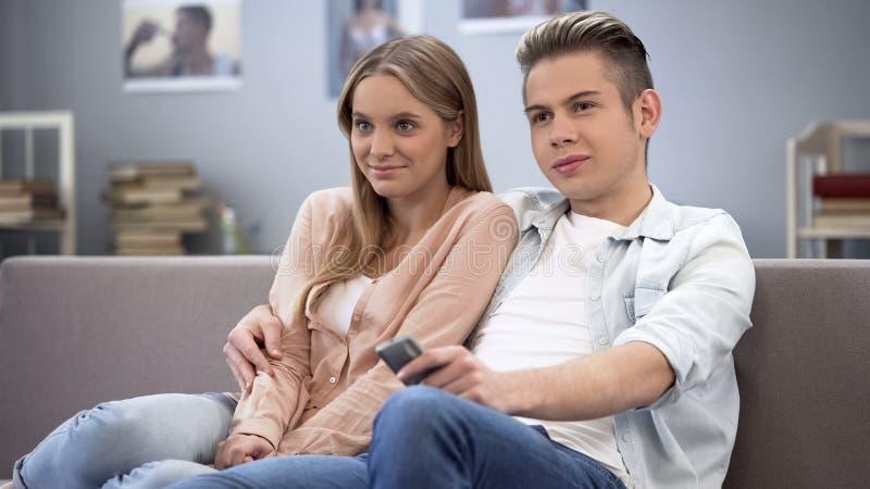 Pares jovenes en el amor que abraza en el sofá, tiempo del gasto junto, viendo la TV fotografía de archivo libre de regalías