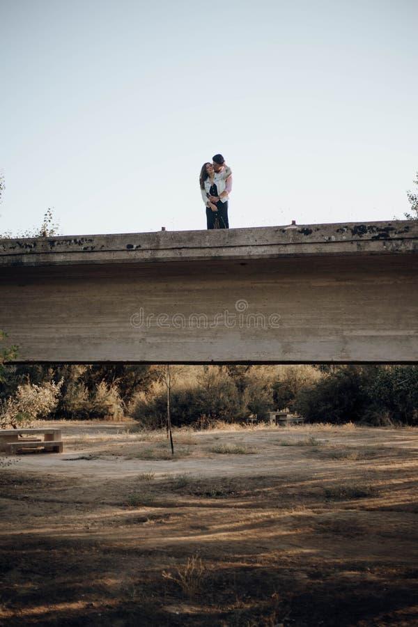 Pares jovenes en el amor que abraza en un puente viejo imagen de archivo libre de regalías