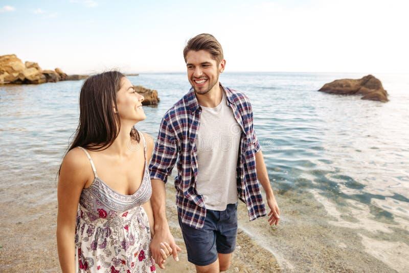 Pares jovenes en el amor que camina en la playa que lleva a cabo las manos imágenes de archivo libres de regalías