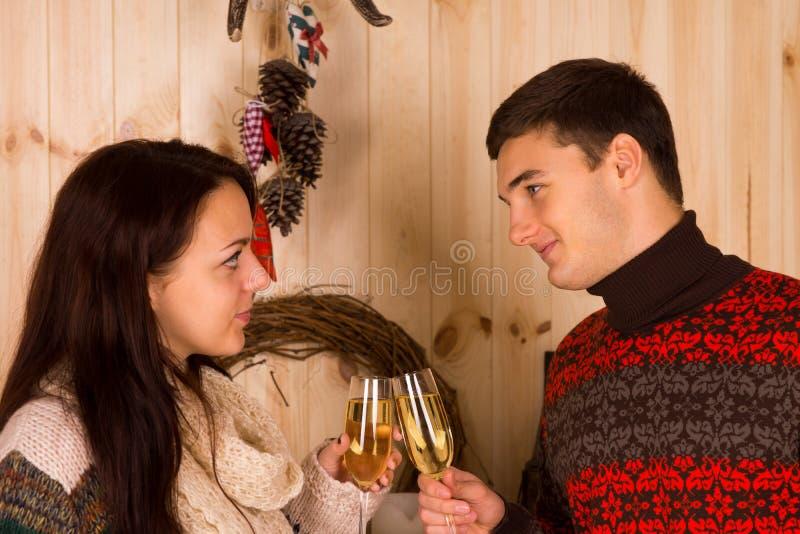 Pares jovenes en el amor que celebra con champán imagenes de archivo