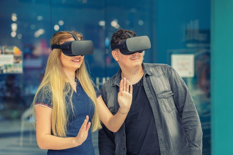 Pares jovenes en el amor que conecta a través de los vidrios de la realidad virtual en centro del patio fotos de archivo