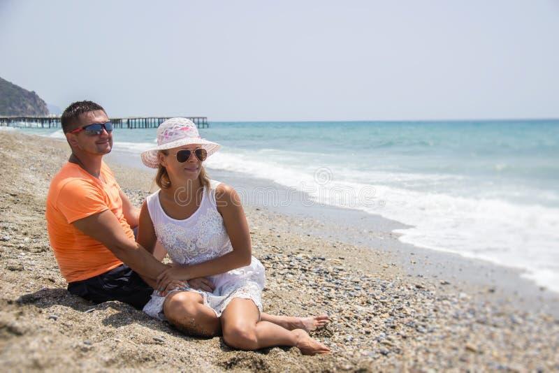 Pares jovenes en el amor que miente en la playa, gozando imagen de archivo libre de regalías
