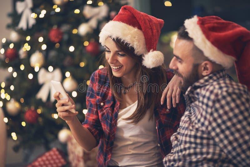 Pares jovenes en el amor que mira el teléfono celular junto imagenes de archivo