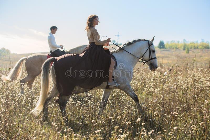 Pares jovenes en el amor que monta un caballo imagen de archivo libre de regalías