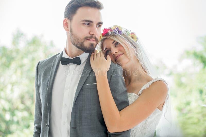 pares jovenes en el amor que se casa la novia y al novio que abrazan junto y que miran uno a que se besa en el parque newlyweds p imagen de archivo