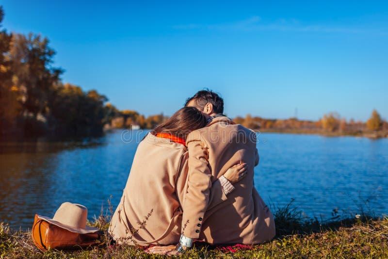 Pares jovenes en el amor que se enfría por el lago del otoño Hombre feliz y mujer que disfrutan de la naturaleza y del abrazo foto de archivo libre de regalías