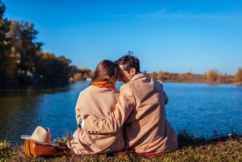 Pares jovenes en el amor que se enfría por el lago del otoño Hombre feliz y mujer que disfrutan de la naturaleza y del abrazo imagenes de archivo