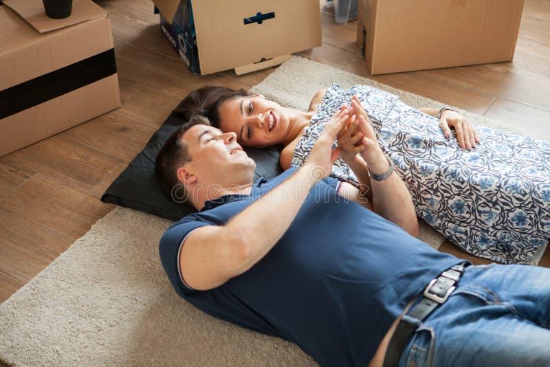 Pares jovenes en el amor que se mueve en su nuevo apartamento fotografía de archivo libre de regalías