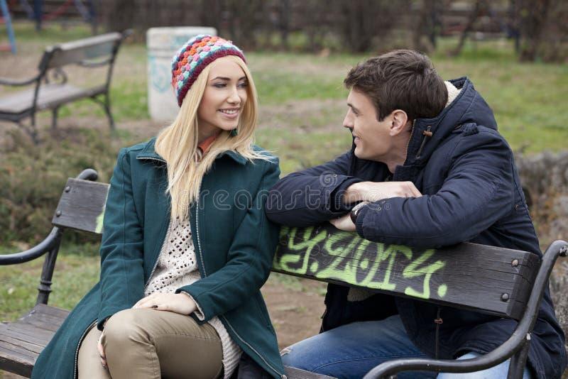 Pares jovenes en el amor que se sienta junto en el banco en el parque imagen de archivo