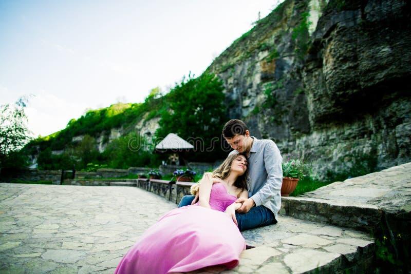Pares jovenes en el amor que se sienta junto en un banco en parque del verano Futuro feliz, conceptos de la boda vendimia fotografía de archivo libre de regalías