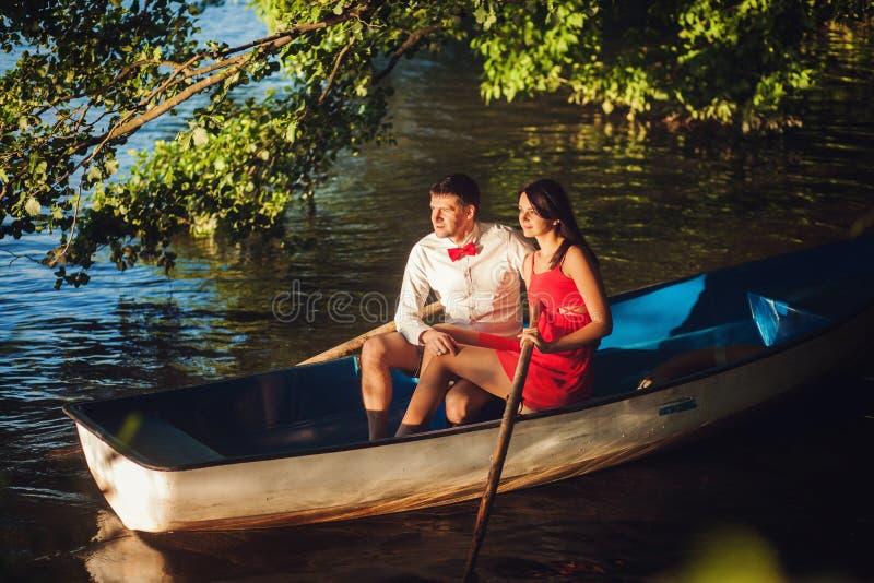 Pares jovenes en el amor que se sienta en un barco fotografía de archivo libre de regalías