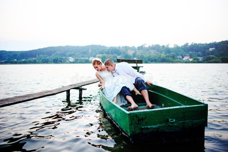 Pares jovenes en el amor que se sienta en un bote pequeño y que se divierte imágenes de archivo libres de regalías