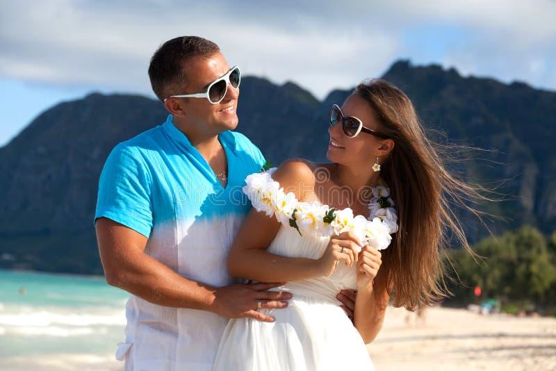 Pares jovenes en el amor que siente feliz en la playa hawaiana fotos de archivo libres de regalías