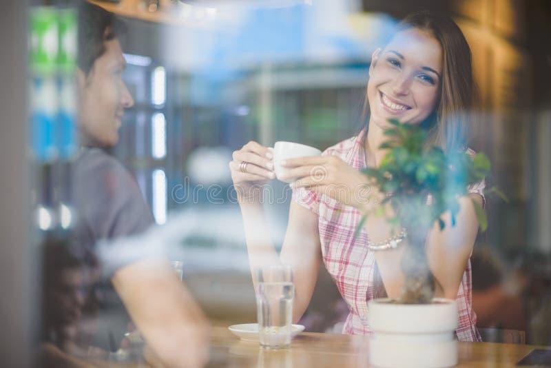 Pares jovenes en el café de consumición de la primera fecha fotografía de archivo