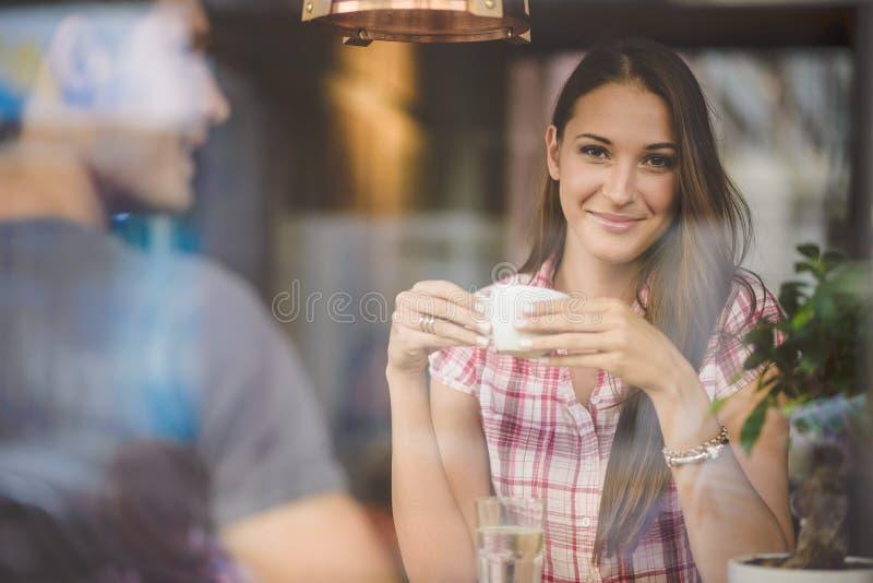 Pares jovenes en el café de consumición de la primera fecha imagenes de archivo