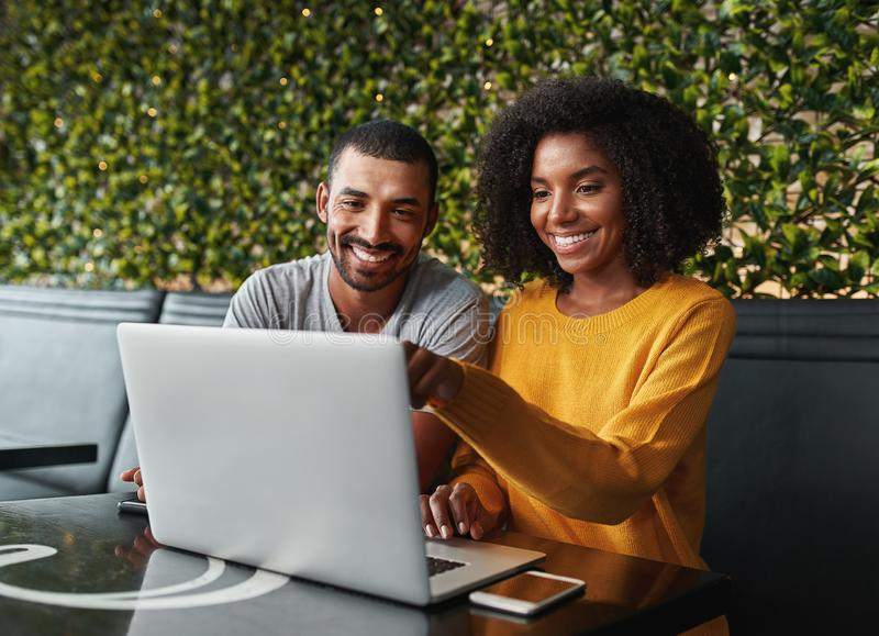 Pares jovenes en el café que mira el ordenador portátil foto de archivo