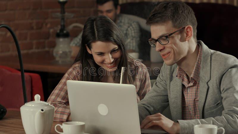 Pares jovenes en el café que mira el ordenador portátil y que fuma la cachimba foto de archivo