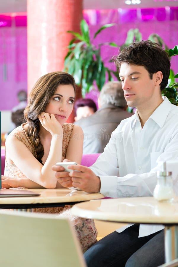 Pares jovenes en el café que no obra recíprocamente pero en el teléfono imagenes de archivo