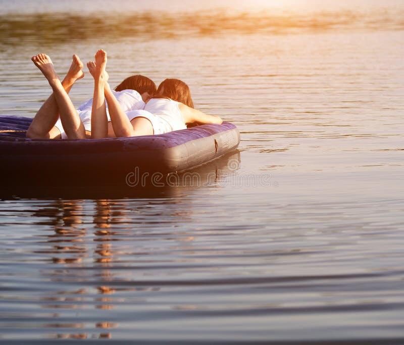 Pares jovenes en el colchón de la natación imagen de archivo