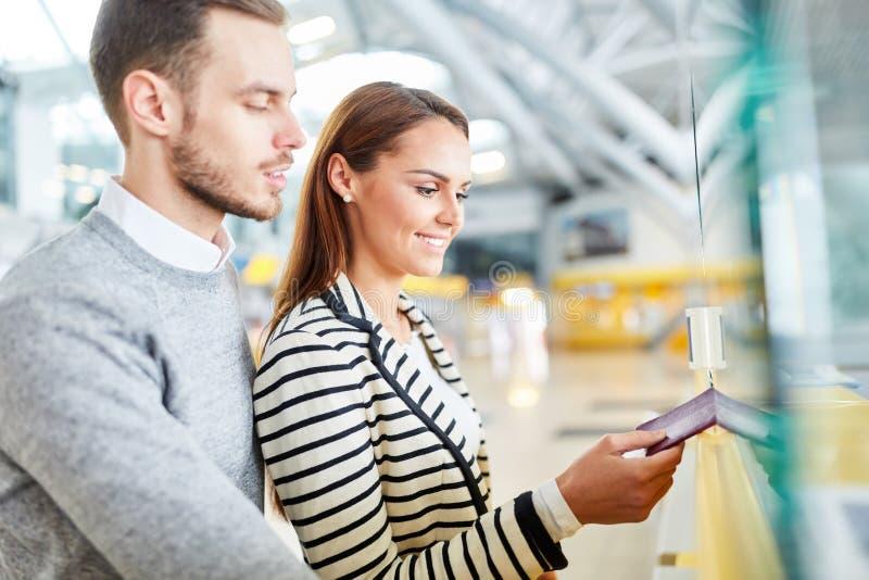 Pares jovenes en el contador del incorporar del aeropuerto imagen de archivo