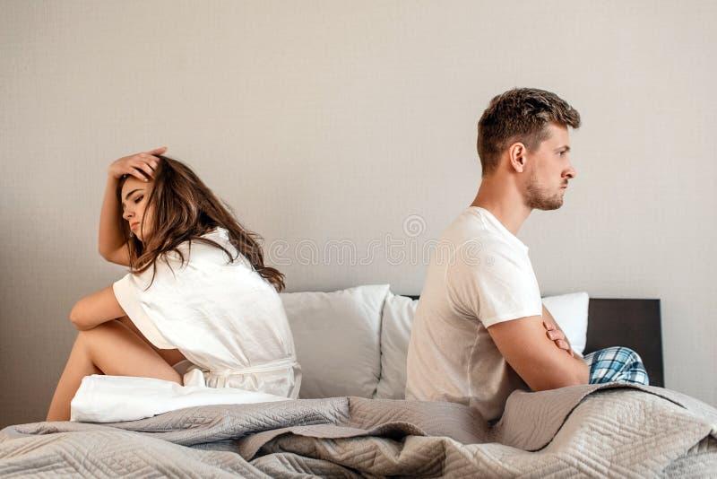 Pares jovenes en el dormitorio El hombre y la mujer infelices se están sentando de nuevo a la parte posterior en la cama, escena  foto de archivo libre de regalías