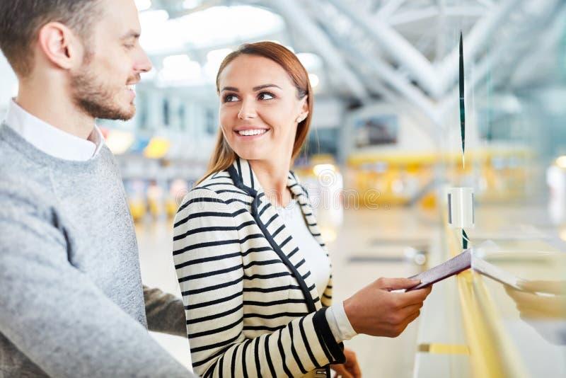 Pares jovenes en el escritorio del incorporar en el aeropuerto imagenes de archivo