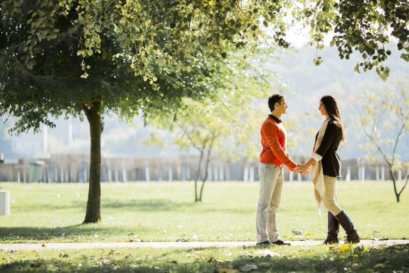 Pares jovenes en el parque del otoño imagenes de archivo