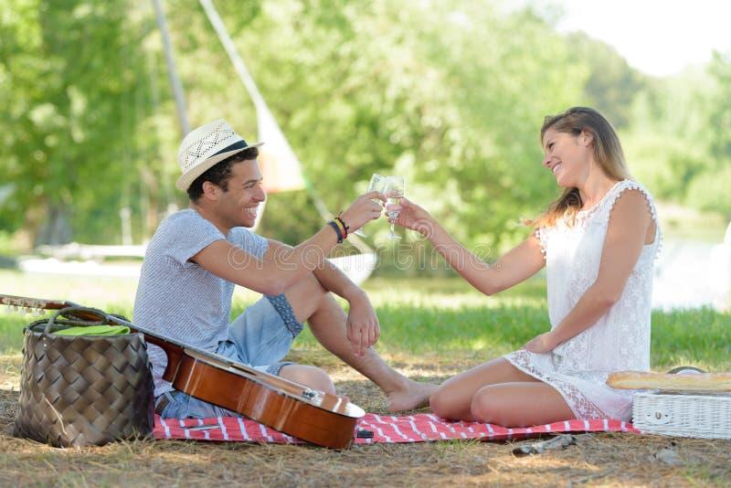 Pares jovenes en el parque que anima durante comida campestre imagen de archivo libre de regalías