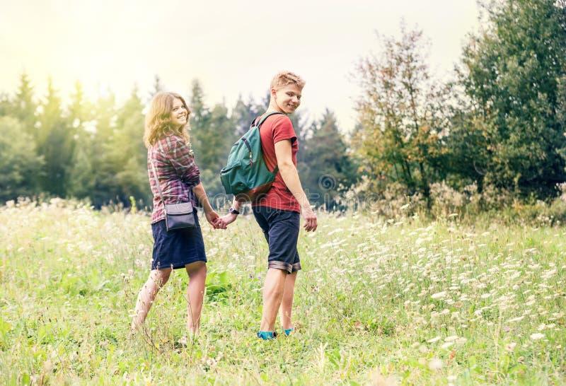 Pares jovenes en el paseo en bosque del verano foto de archivo
