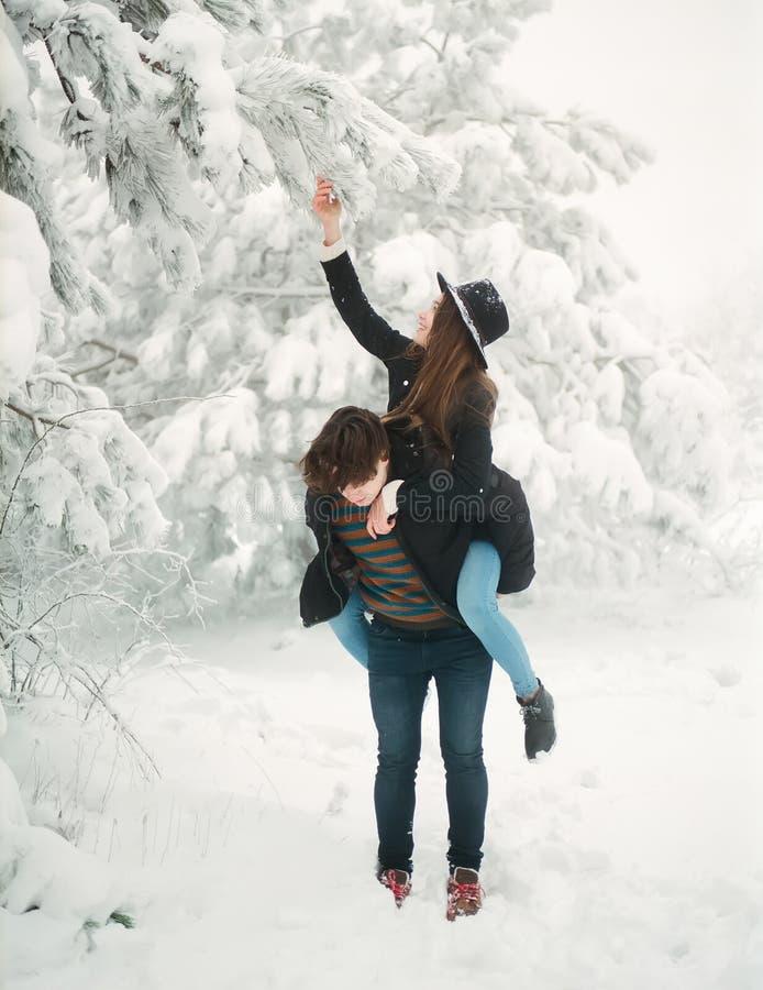 Pares jovenes en el winterwear que disfruta de las nevadas Historia de amor imagenes de archivo