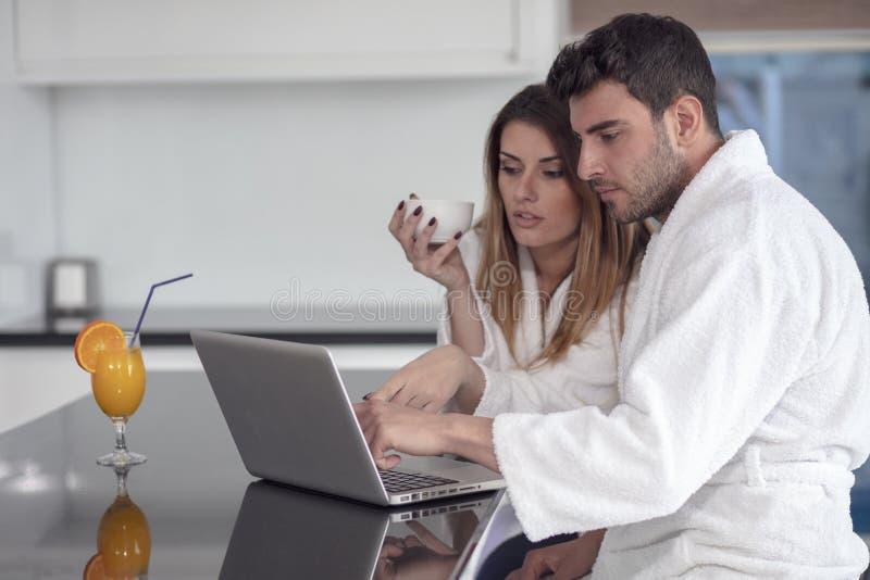 Pares jovenes en la albornoz en casa que come café en la cocina y que trabaja en el ordenador portátil imagenes de archivo