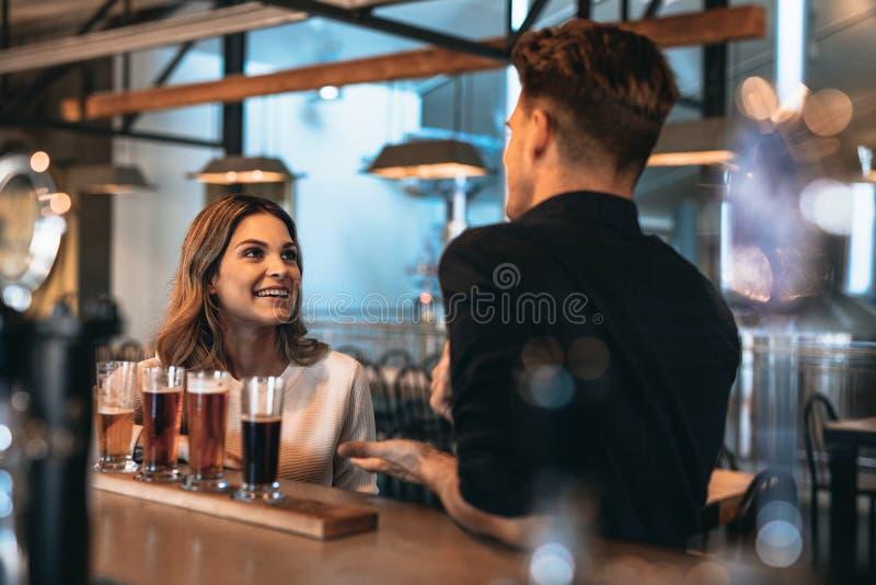 Pares jovenes en la barra con diversas cervezas del arte fotos de archivo libres de regalías