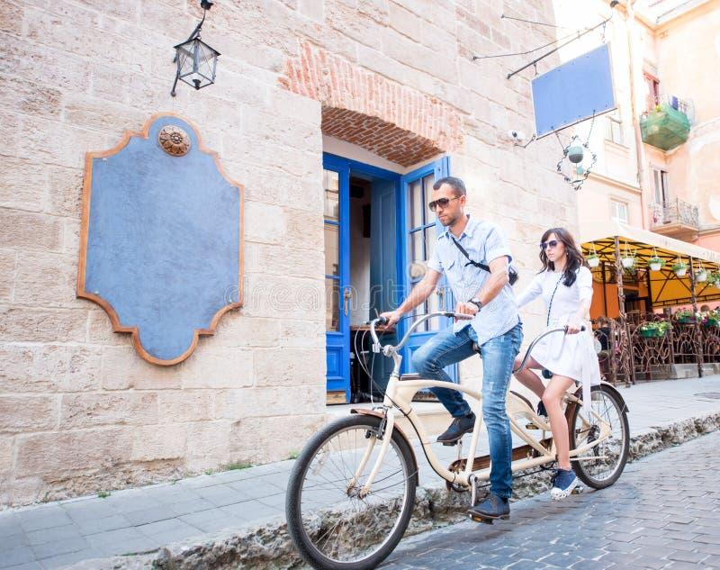 Pares jovenes en la bicicleta en tándem en la ciudad de la calle imágenes de archivo libres de regalías