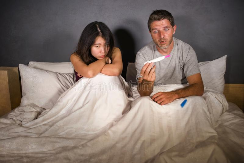 Pares jovenes en la cama asustada y subrayada después de resultado positivo en prueba de embarazo con la mujer embarazada que cue fotos de archivo libres de regalías