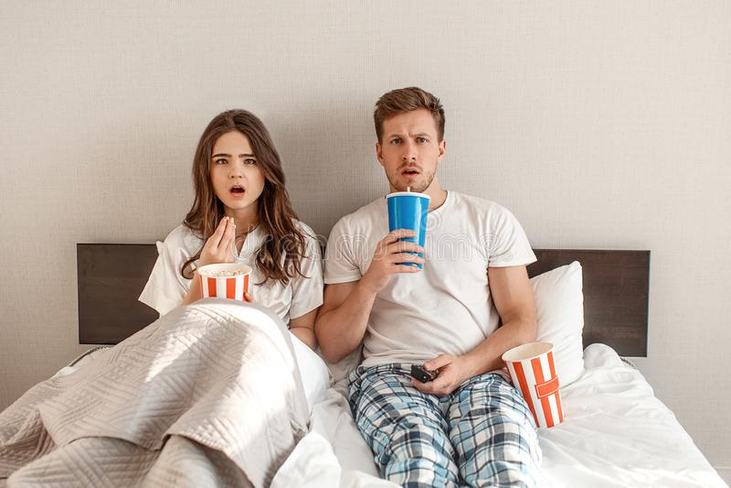 Pares jovenes en la cama Un hombre y una mujer hermosos sorprendidos están comiendo las palomitas y la TV de observación juntos e fotos de archivo libres de regalías