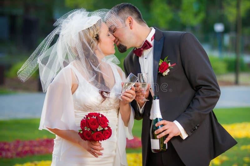 Pares jovenes en la celebración del amor en jardín foto de archivo
