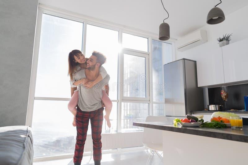 Pares jovenes en la cocina, hombre hispánico Carry Asian Woman Modern Apartment de los amantes fotografía de archivo