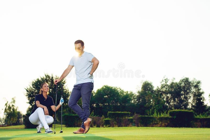 Pares jovenes en la corte del golf imagenes de archivo