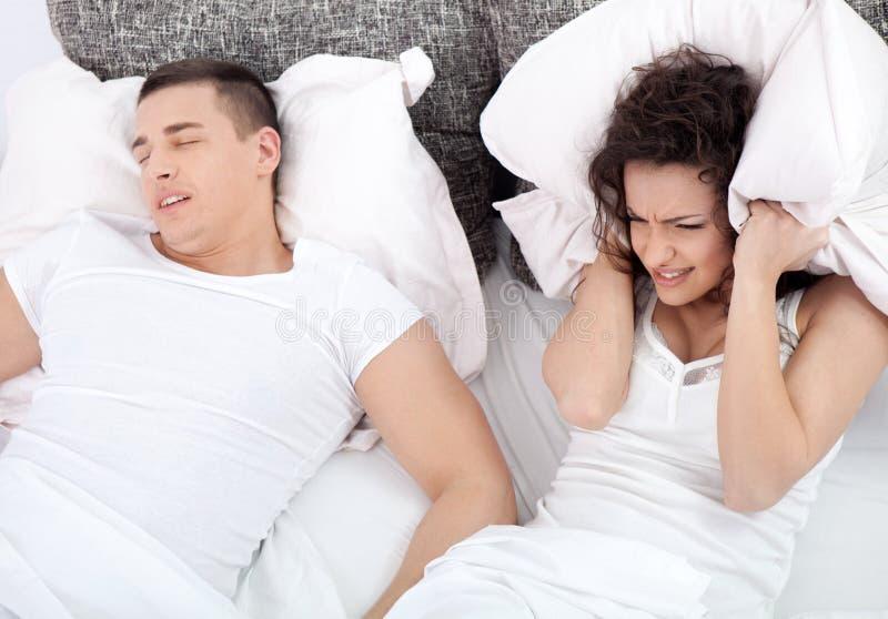 Pares jovenes en la mujer de la cama que intenta dormir mientras que está roncando un hombre imagen de archivo