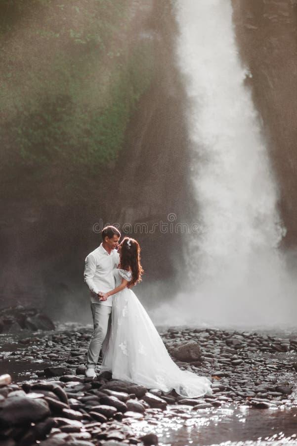 Pares jovenes en la novia y el novio, d?a del amor de boda cerca de una cascada de la monta?a imagen de archivo