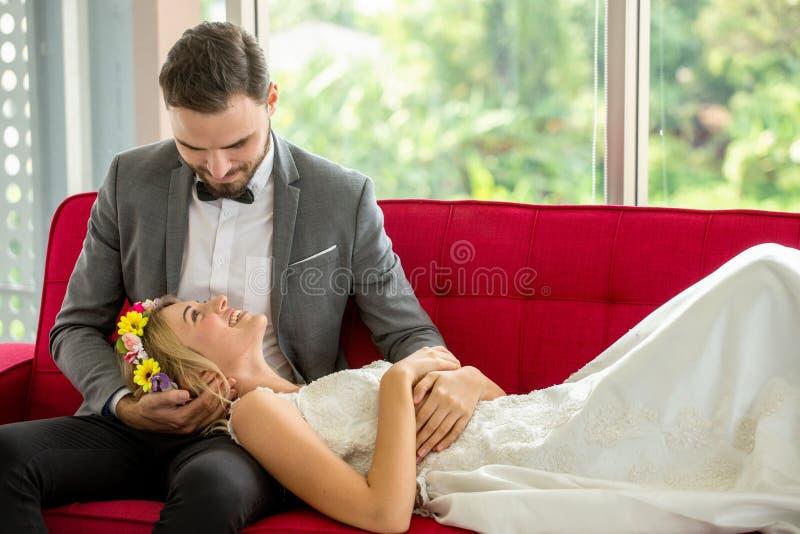 pares jovenes en la novia y el novio de la boda del amor que se acuestan en el sofá rojo junto que parece uno a newlyweds Retrato foto de archivo