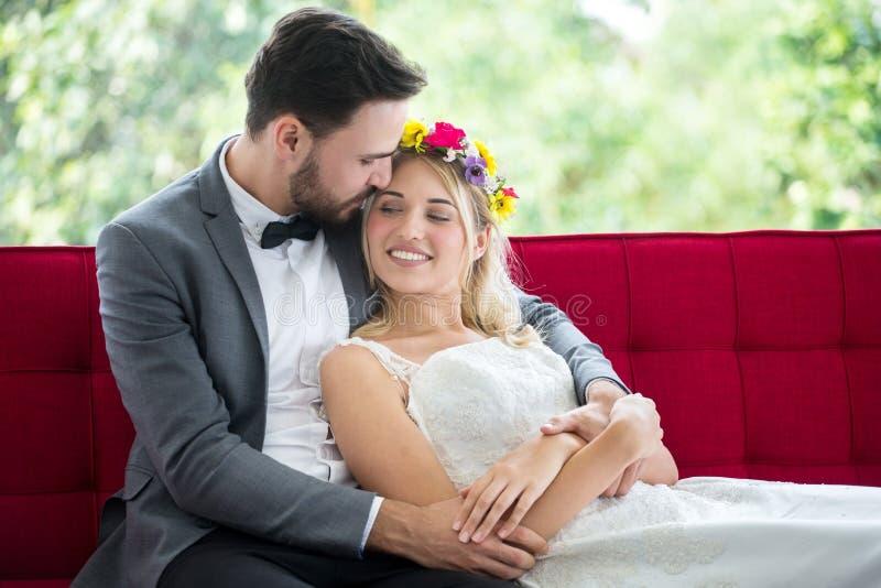 pares jovenes en la novia y el novio de la boda del amor que se acuestan en el sofá rojo que mira uno a y que abraza junto newlyw imagen de archivo libre de regalías