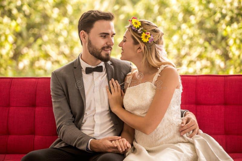 pares jovenes en la novia y el novio de la boda del amor que se sientan en el sofá rojo que mira uno a y que abraza junto newlywe imagen de archivo libre de regalías