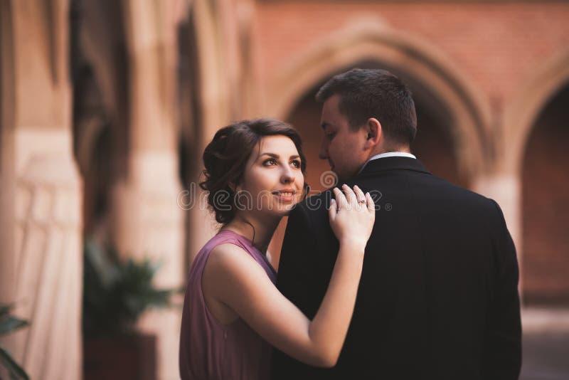 Pares jovenes en la novia y el novio del amor que presentan cerca de área con las columnas blancas en el fondo kraków fotografía de archivo